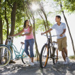 Pacific Islander couple walking bicycles on beach — Stock Photo