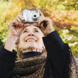 Senior woman taking photograph outdoors — Stock Photo