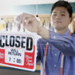 Asian drycleaner putting up closed sign — Stock Photo #23252842