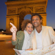 Couple looking at map in Paris at night — Stock Photo
