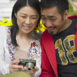 Asian couple looking at digital camera and smiling — Stock Photo