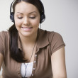 Teenaged Hispanic girl listening to music on headphones — Stock Photo