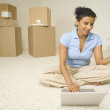 Indian woman shopping online in new house — Stock Photo