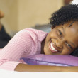 Young African woman laying on bed smiling — Stock Photo