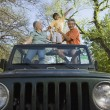 Grandparents and grandson standing in jeep - Stock Photo