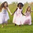 Young girls wearing party dresses and running in field — ストック写真