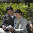 Asian couple looking at guide book in park — Stock Photo