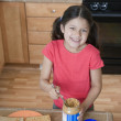 Hispanic girl making peanut butter and jelly sandwich — Stock Photo