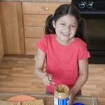 spansktalande tjej att göra jordnötssmör och gelé smörgås — Stockfoto