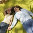 Mother and daughter laying on picnic blanket — Stock Photo