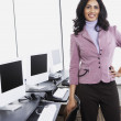 Indian businesswoman standing next to computers smiling — Stock Photo