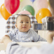 Mother video taping baby in high chair — Stock Photo