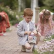 Children gathering Easter eggs in garden — Stok fotoğraf