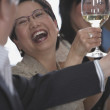 Friends laughing and toasting with white wine — 图库照片