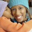 Stock Photo: AfricAmericgirl kissing mother