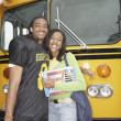 Young African man in football uniform with girlfriend next to school bus — Stock Photo
