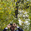 Senior African man using binoculars in woods — Stock Photo
