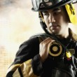 Male fire fighter in front of burning building — Stock Photo #23253366