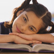 Young Hispanic girl at desk in classroom - Stockfoto