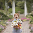 Young boy holding flowers in garden - Stock Photo