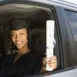African woman in car wearing graduation outfit — Stock fotografie