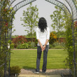 Woman standing in archway in garden - Stock Photo