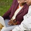 Senior African couple using laptop outdoors — Stock Photo #23253484