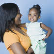 Studio shot of African mother holding young daughter — Stock Photo