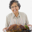 Senior Hispanic woman holding roasted turkey in pan — Stock Photo