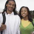 Stock Photo: Young Africcouple smiling with school books