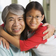 Asian grandfather hugging granddaughter indoors — Stock Photo
