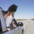 Woman leaning out of car window on deserted road — Stock Photo #23253636