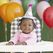 African baby in high chair wearing party hat - Stock Photo