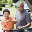Hispanic father and son checking oil in car — Stock Photo