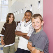 Boys smiling and leaning on school lockers - Stockfoto
