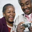 Senior African couple smiling and looking at digital camera — Stock Photo