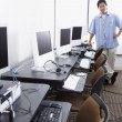 Young Asian man standing next to computer stations — Stock Photo