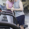 Royalty-Free Stock Photo: Couple standing on treadmill at gym