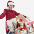 Senior Hispanic woman with shopping cart full of gifts — Stock Photo #23253742