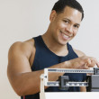 African American man weighing himself on scale — Stock Photo #23253774