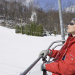 Woman smiling on ski lift — Stock Photo