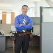 Senior Asian businessman wearing tool belt in office cubicle — Stock Photo