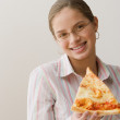 Hispanic girl eating slice of pizza — Stock Photo