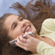 Hispanic girl laying down using cell phone — Stock Photo