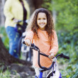 Young girl on bicycle in woods — Stock Photo #23253932