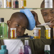 African father taking son's temperature in front of medicine cabinet — Stock Photo #23253942
