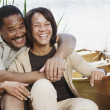 Middle-aged African couple laughing next to canoe - Stock Photo