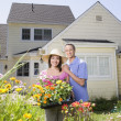 Couple with flat of plants in yard — Stock Photo