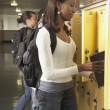 Group of students putting books in school lockers — Stock Photo