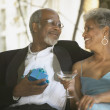 Senior African couple in formal dress with gift and cocktail — Stock Photo #23254054